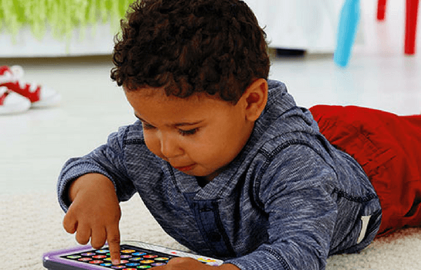 young boy playing with fisher-price smart stages tablet