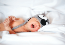 baby sleeping on white sheets with hat on its head