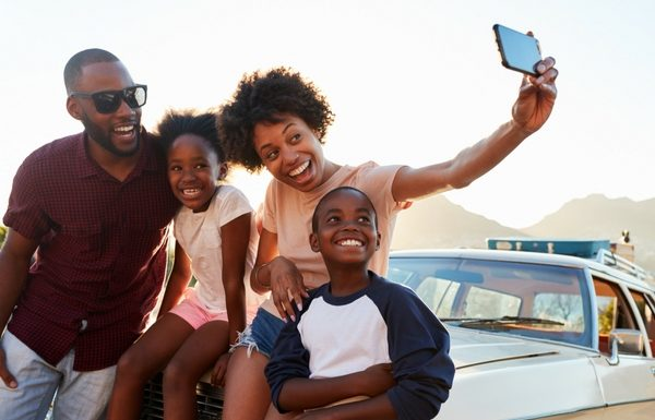 happy family taking a selfie on the bonnet of a car before they go on their road trip with their children