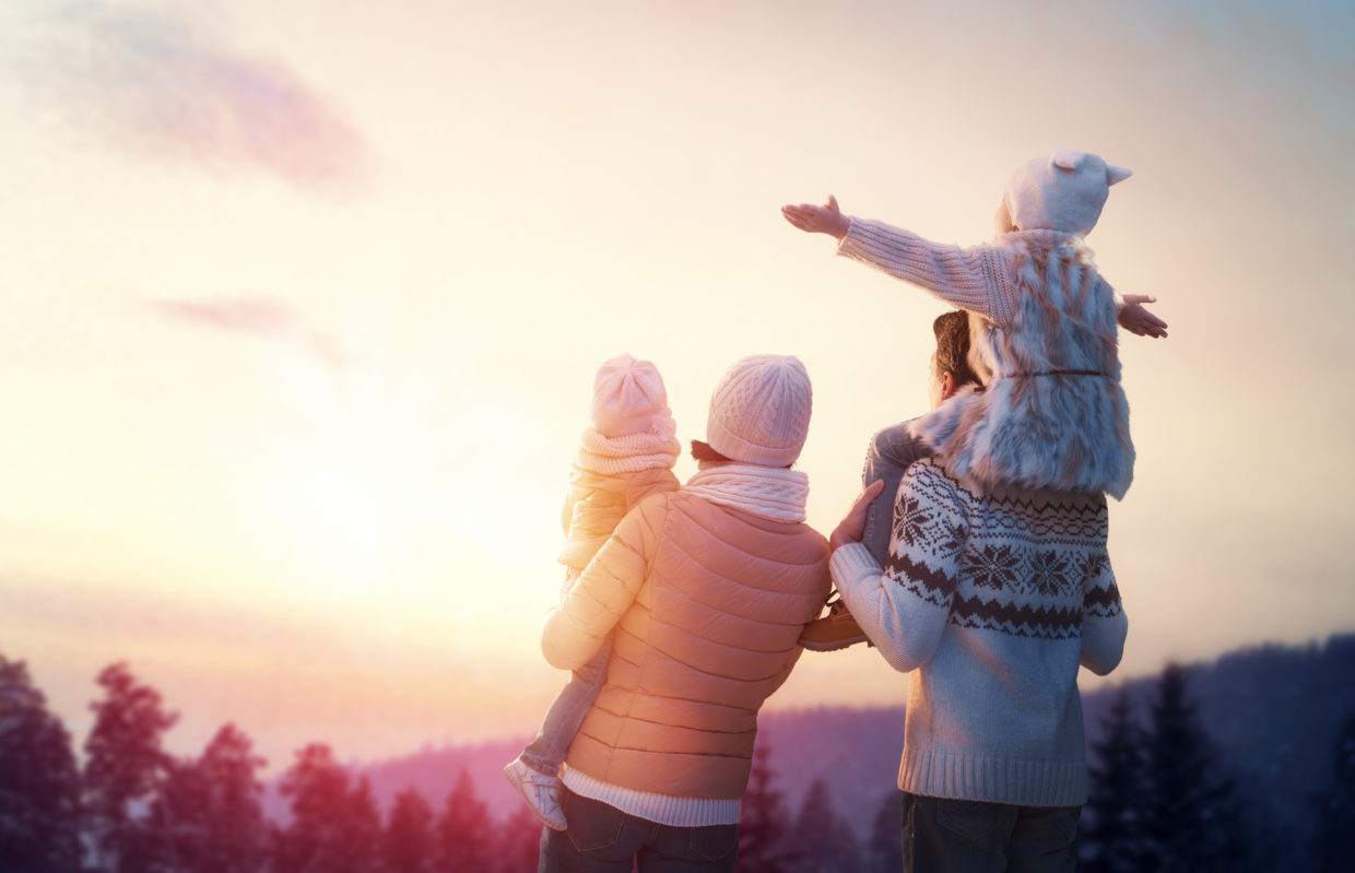 family wearing winter clothes looking at sunset