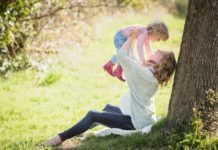happy mother sitting by a tree with her little child in her arms in the air smiling and laughing being a better human