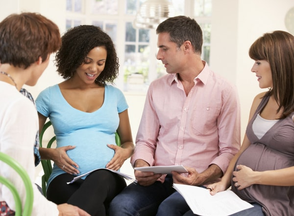 antenatal class with mother holding her tummy while other people look at her-min