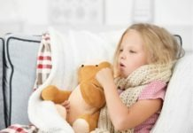 little blonde girl who had her tonsils out sitting on a couch with teddy while coughing