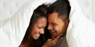man and woman under covers smiling masturbation month