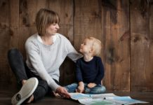 mother sitting with child looking at map on floor with wooden wall-min