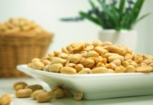peanuts on white plate with green plant in background