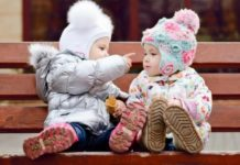 two babies in winter clothes talking and cooing with each other on a bench-min