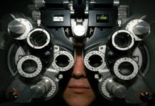 person looking through optometrist equipment