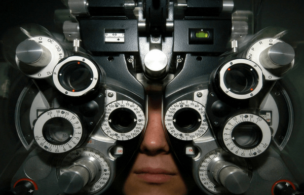 person looking through optometrist equipment