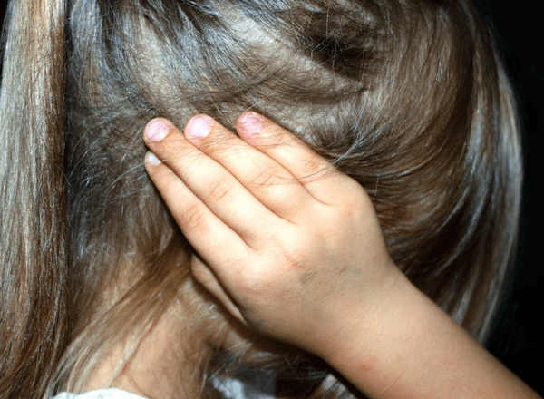 girl holding her hands over her ears