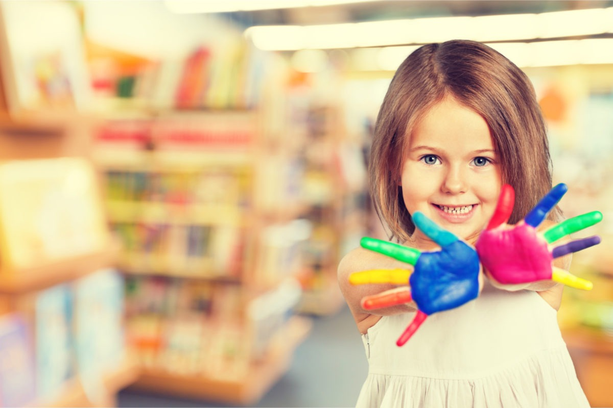 preschooler girl with multicoloured painted hands with blurry library background