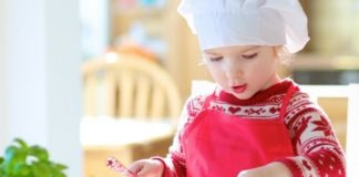 child wearing red apron making pizza with tomato sauce topping and cheese in bright sunny room