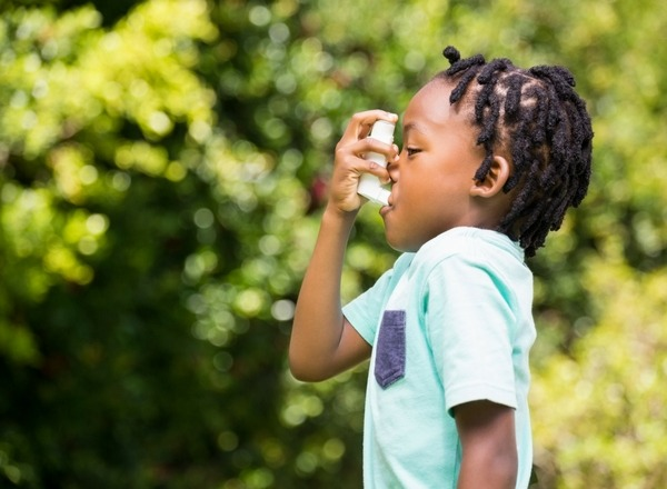 little boy in blue green shirt using an asthma inhaler while in the garden