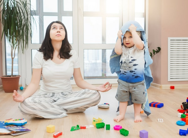 mother on floor meditating exercising patience while toddler making a mess and playing on floor with towel over his head-min