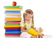 preschooler girl reading a book sitting next to a pile of books with an apple