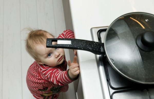 small child baby reaching up to hot pot on stove about to be burned-min