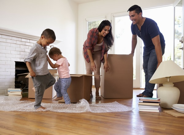 happy family moving house by packing boxes