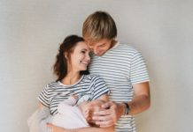 breastfeeding with dad and mom standing smiling