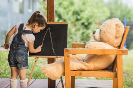 special needs child drawing on chalk board