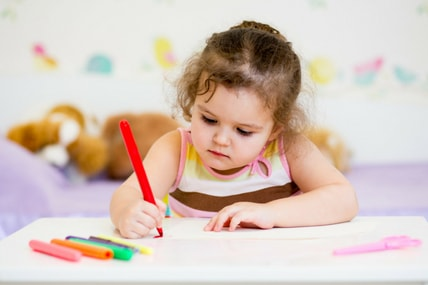 special needs child writing with coloured crayons