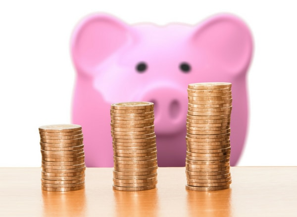teaching cents piggy bank with coins piled in front of it