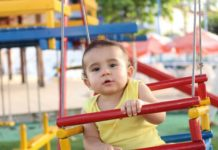 baby in swing being looked after by au pair