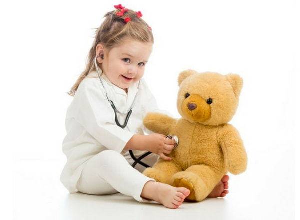 sick child playing with stethoscope and teddy bear-min