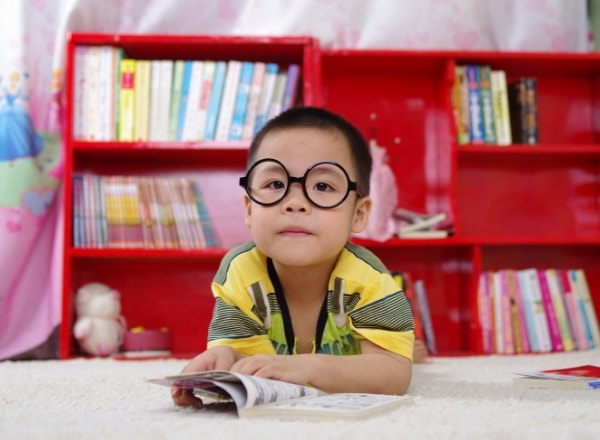 boy-reading-infront-of-bookshelf