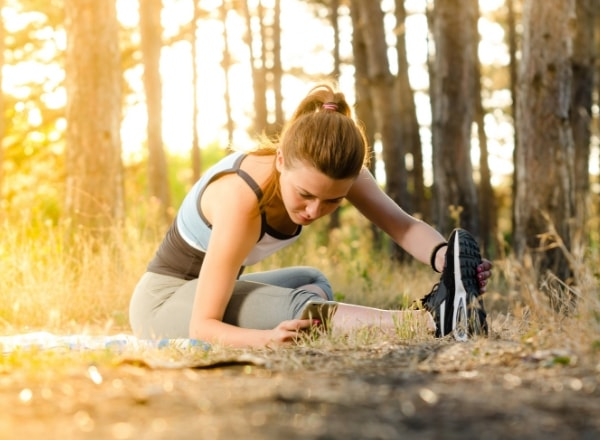 lady-getting-in-shape-for-Spring-in-woods-stretching