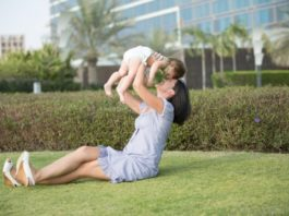 mom-with-child-on-grass-lawn