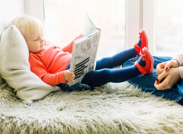 toddler-girl-reading-book