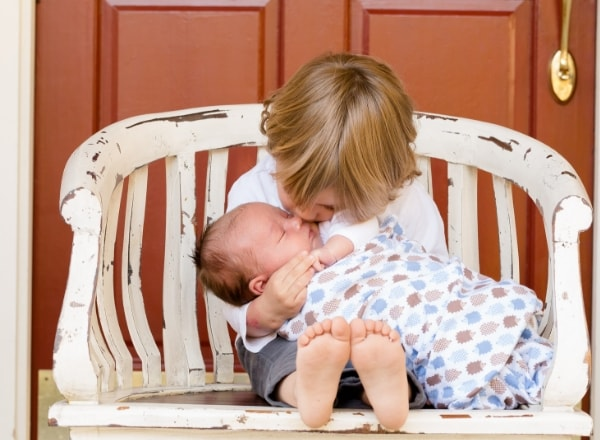 brother-kissing-sibling-baby