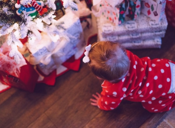 baby-with-christmas-presents-under-tree