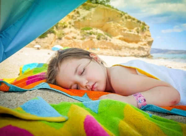 girl-child-sleeping-on-the-beach