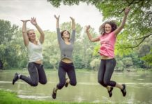 ladies-jumping-in-park-by-lake