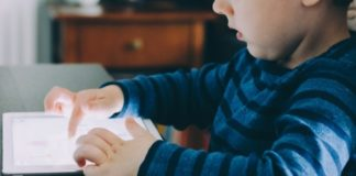 child-using-electronic-tablet-to-access-social-media