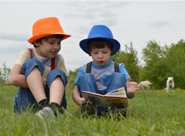 children-reading-in-a-field