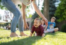 mother-with-baby-and-kids-playing-on-grass