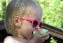 toddler-wearing-pink-sunglasses-eating-an-apple