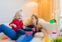 exhausted mom lying on a couch with her daughter