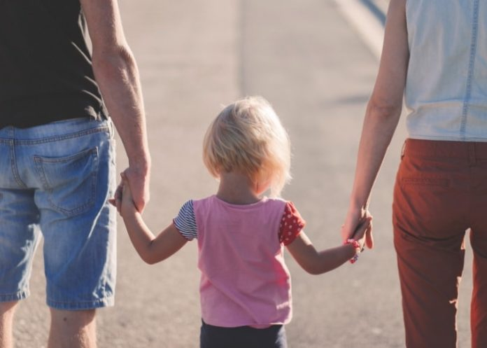 child-with-parents-holding-hands