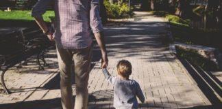 dad-holding-toddler-arm-while-walking