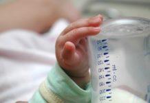 baby-holding-formula-bottle