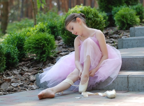 confident-pre-schooler-putting-on-ballet-shoes