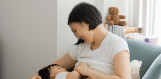 Mom breastfeeding baby for debate on breastfeeding or formula feeding