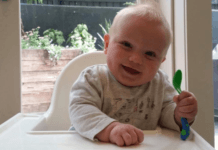 baby-in-highchair-ready-to-start-weaning-onto-solids-happy-smile-holding-spoon