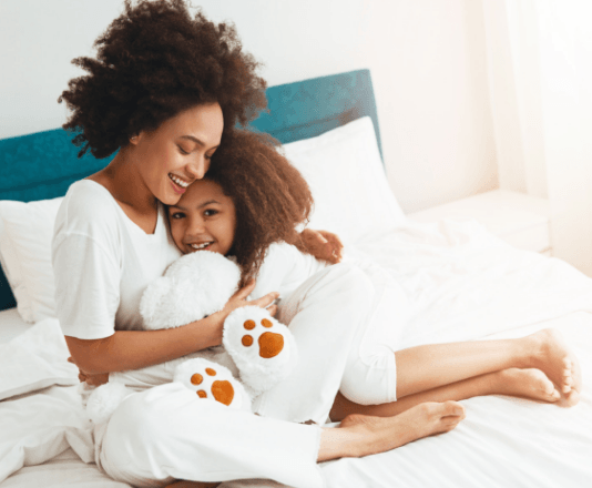 happy-mother-with-daughter-sharing-cuddles-on-white-bed-with-teddy-bear