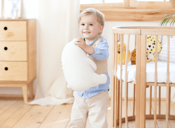 happy-toddler-in-eco-friendly-nursery-holding-stuffed-animal-smiling