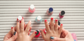 mom-painting-girl-toddlers-fingernails-with-nailpolish-in-different-colours