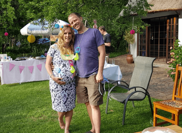mom-pregnant-with-twin-babies-at-baby-shower-with-husband-smiling